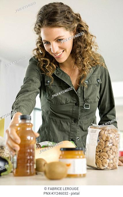 Woman holding a bottle of olive oil in the kitchen