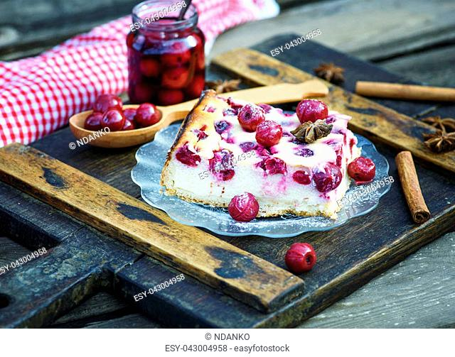 piece of cottage cheese cake and cherry berries on a glass plate and canned cherry berries