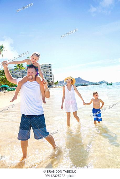 A family of four enjoying a summer vacation in Waikiki Beach; Honolulu, Oahu, Hawaii, United States of America