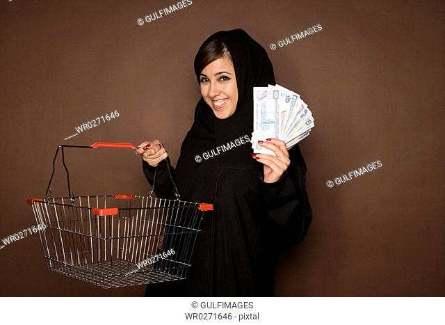Young woman holding shopping cart and paper currency,portrait