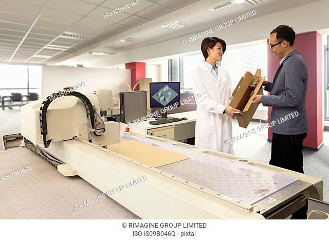 Technician showing cardboard box to manager by packaging machine in printing and packaging factory, China