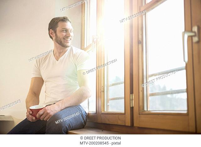 Architect sitting on window sill and having cup of coffee, Bavaria, Germany