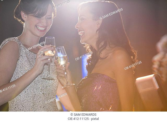 Well dressed women toasting champagne flutes
