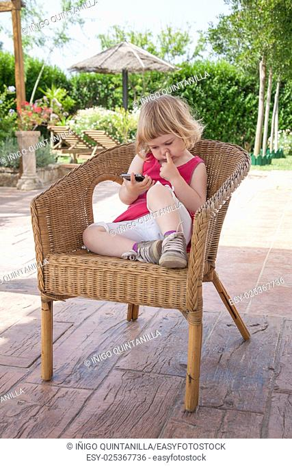 blonde caucasian girl two years old, summer red and white dressed, sitting on wicker chair watching smartphone or mobile phone with finger in nose