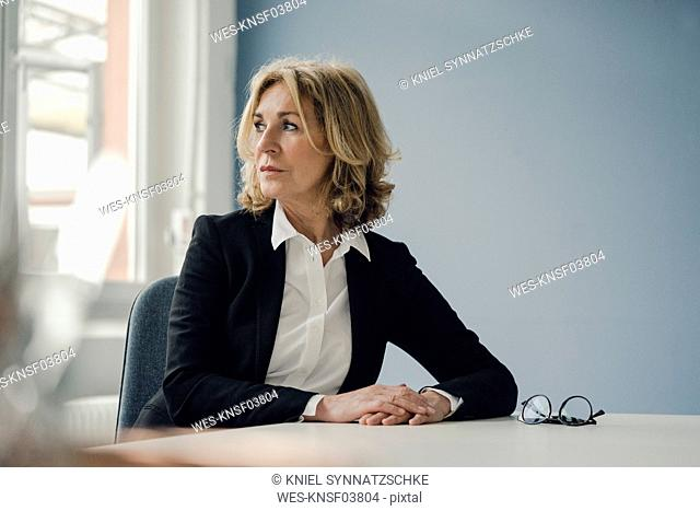 Senior businesswoman sitting at table looking sideways