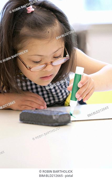 Mixed race Down syndrome student drawing in class