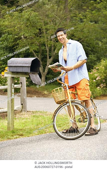 Portrait of a mature man standing with a bicycle near a mailbox