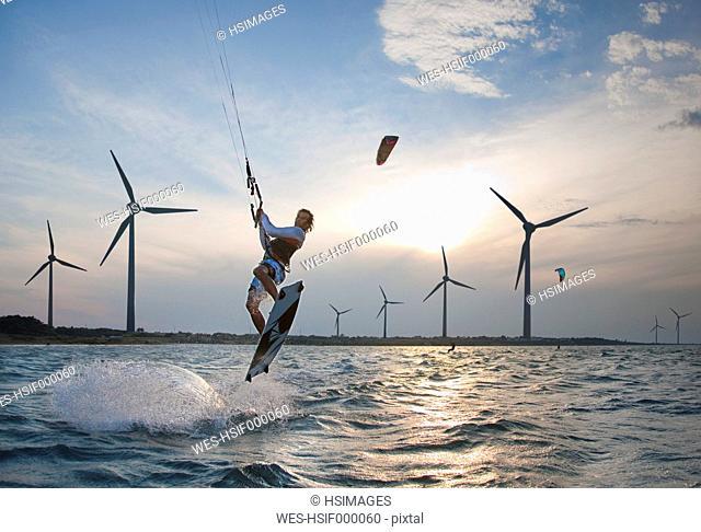 Croatia, Zadar, Kitesurfer jumping in front of wind turbine