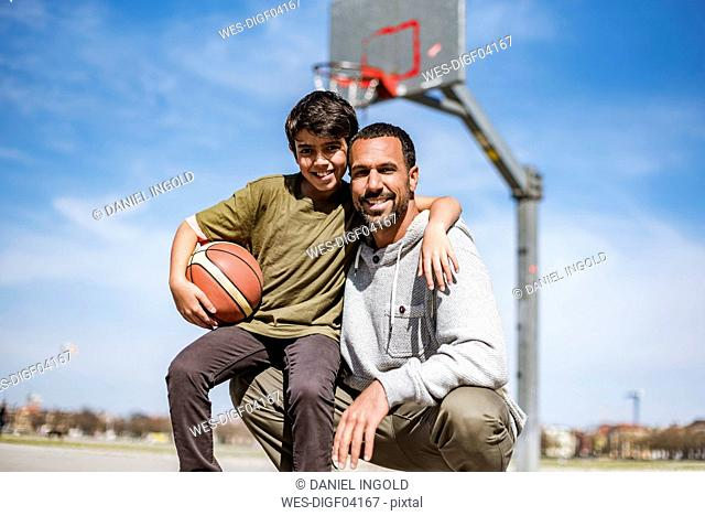 Portrait of happy father and son with basketball outdoors