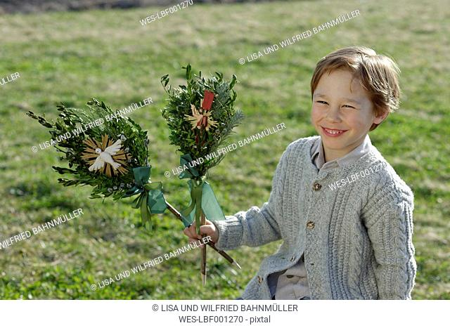 Germany, Upper Bavaria, Portrait of smiling little boy with Palmbusch on a meadow