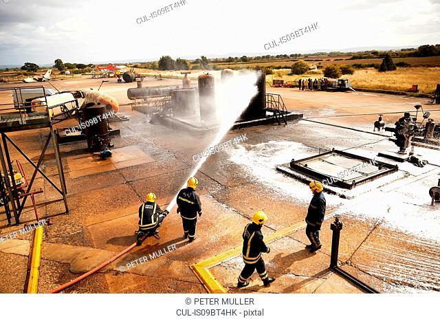 Firemen training, firemen spraying firefighting foam at oil storage tank at training facility