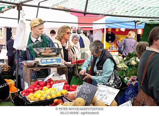 Customer paying for purchases on market fruit and veg stall