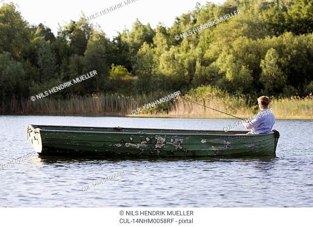 man fishing in rowboat