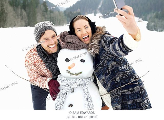Enthusiastic couple taking self-portrait with snowman in snowy field