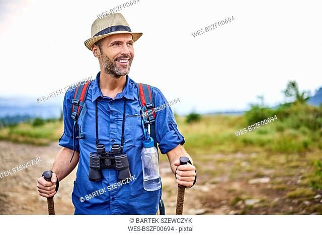 Smiling man with binoculars hiking in the mountains