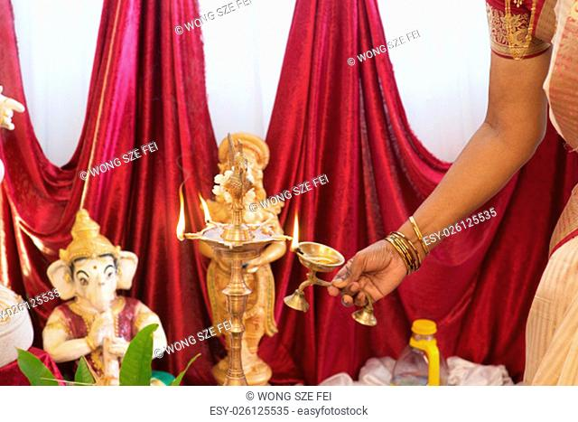 Woman hand lighting up the metal diya. Traditional Indian Hindus religious ceremony. Focus on the oil lamp. India special rituals events