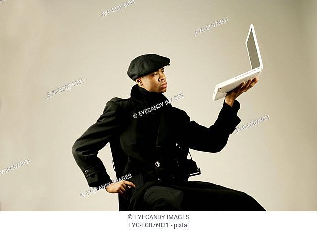 Young African American man holding laptop, studio shot
