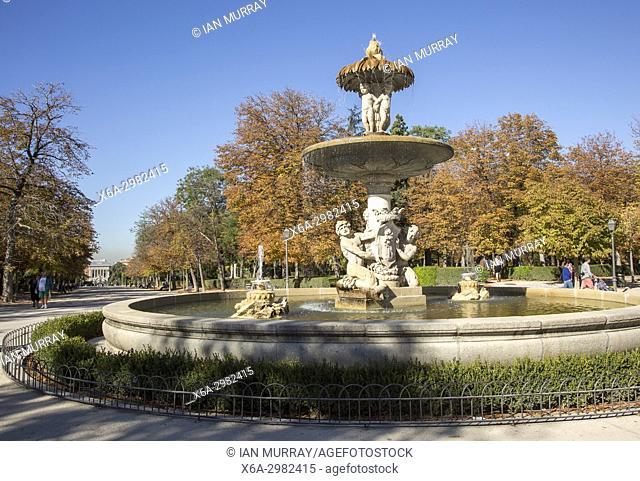 People walking by monument fountain in El Retiro park, Madrid, Spain