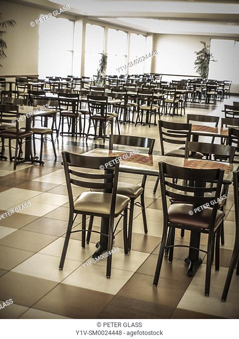 Empty chairs and tables, along with many windows, in a cafeteria