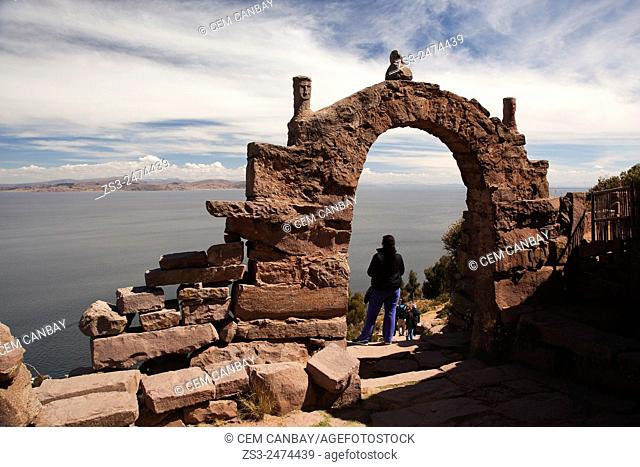 Tourists crossing one of the island's gate and walking down to the harbor, Taquile Island, Titicaca Lake, Puno Region, Peru, South America