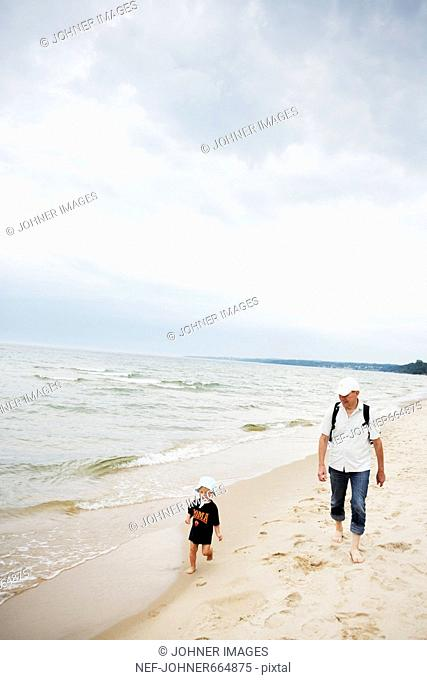 Grandfather and grandson walking on the beach, Sweden