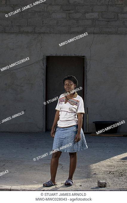 Herero woman,standing outside an unfinnished house framed by a doorway