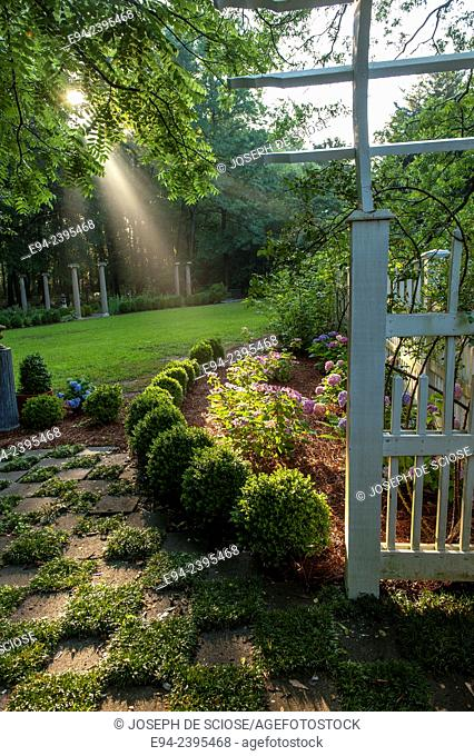 Outdoor living space in a garden setting featuring boxwoods and a white picket fence.Georgia USA