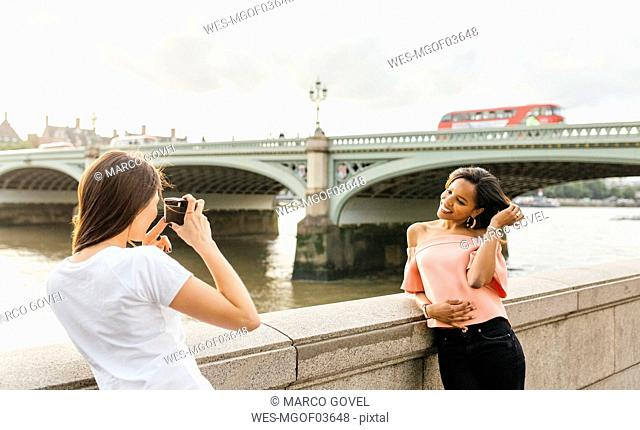UK, London, woman taking a picture of her friend near Westminster Bridge
