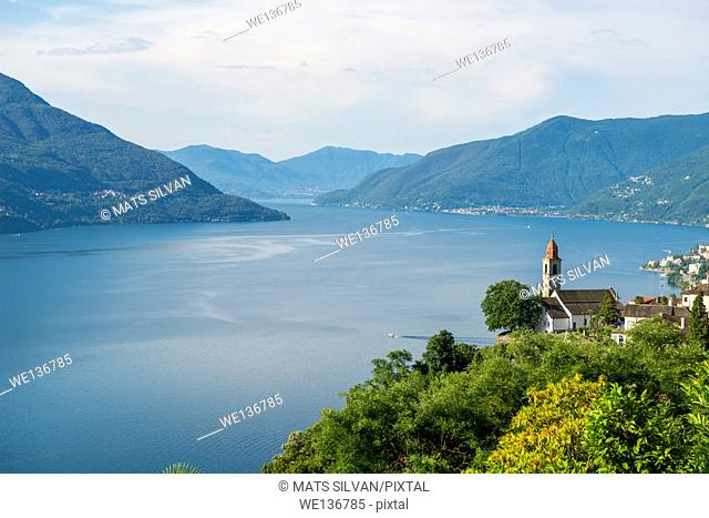 Ronco sopra Ascona with a church over alpine lake Maggiore and mountain in a sunny day in Ticino, Switzerland