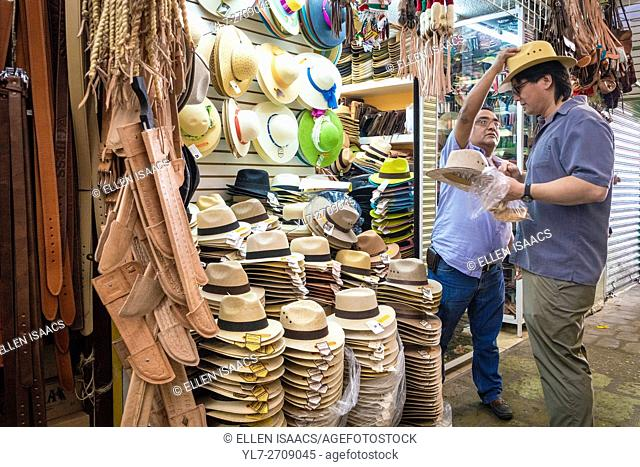Salesman reacing to put a straw hat on a customer at a market in Oaxaca Mexico