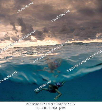 Young boy swimming underwater, split view, Tonga