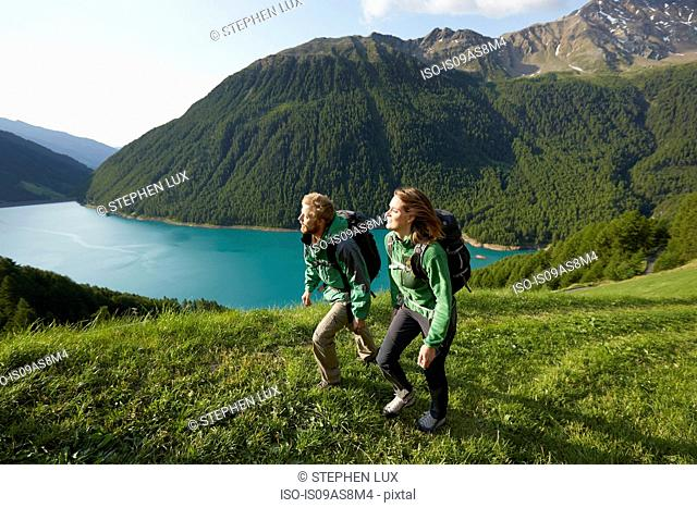 Young couple hiking at Vernagt reservoir, Val Senales, South Tyrol, Italy