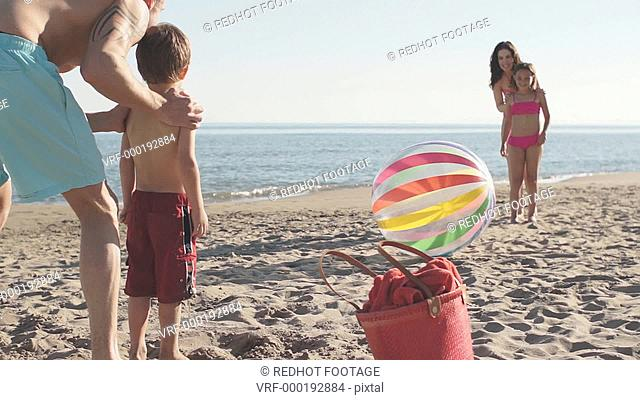 Family playing football with beach ball on beach