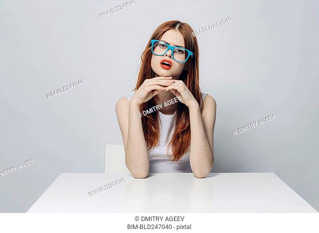 Angry Caucasian woman sitting at table wearing blue eyeglasses