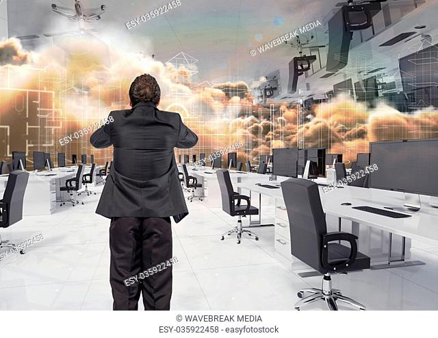 businessman standing in inverted office in the clouds