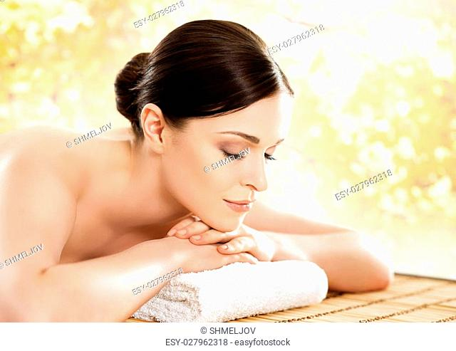 Young and beautiful girl relaxing in spa salon. Massage therapy over seasonal autumn background. Healing medicine and health care concept