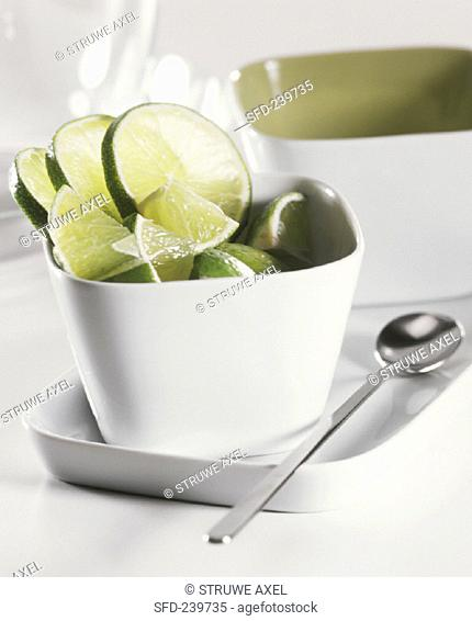 Lime slices and wedges in white bowl