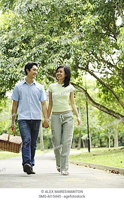 Couple holding hands and walking, man carrying picnic basket