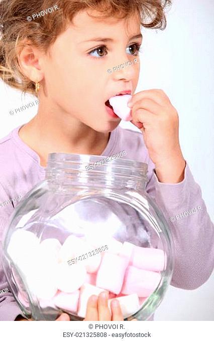 Cute little girl eating marshmallows