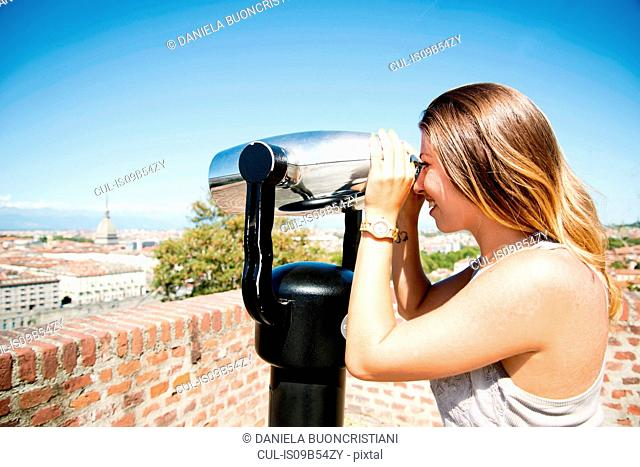 Young woman looking through coin operated binoculars from the Monte dei Cappuccini, Turin, Italy