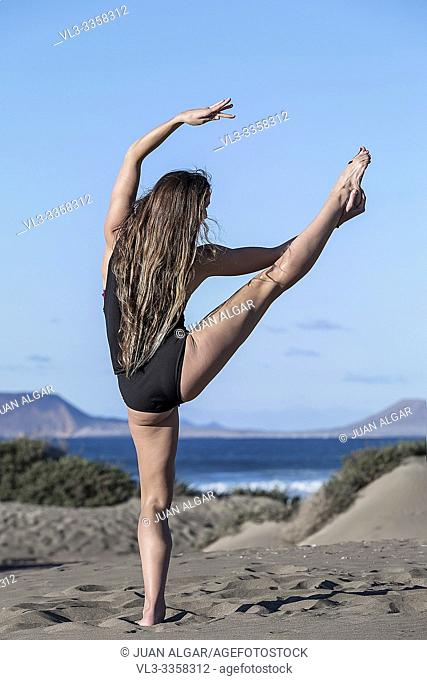 Back view of brunette with long hair showing beautiful asana on seashore against blue sky holding leg raised