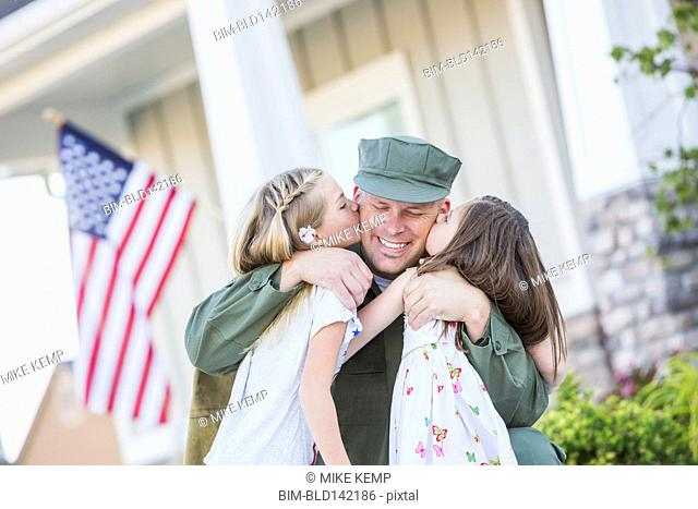 Returning Caucasian soldier hugging daughters
