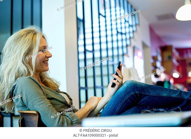 Mature woman relaxing with smartphone