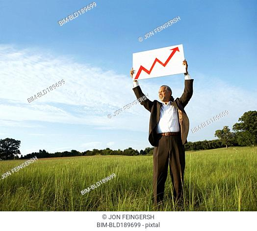 African businessman holding up arrow graph in field