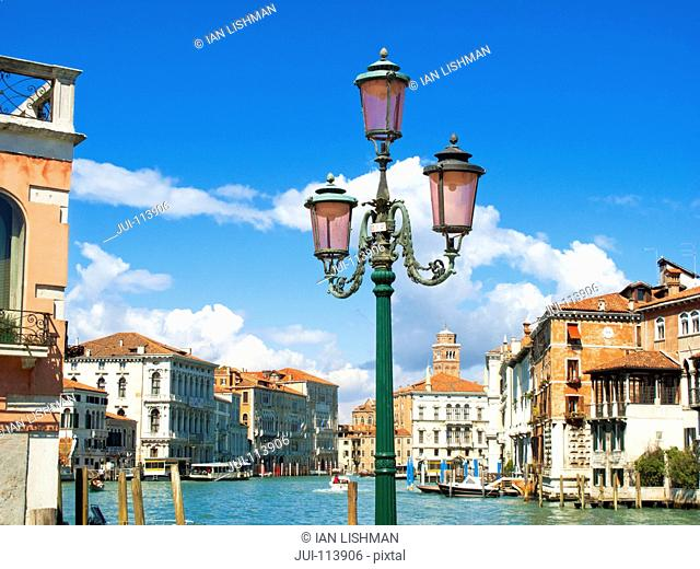 Streetlight and architectural buildings along sunny Grand Canal in Venice, Italy