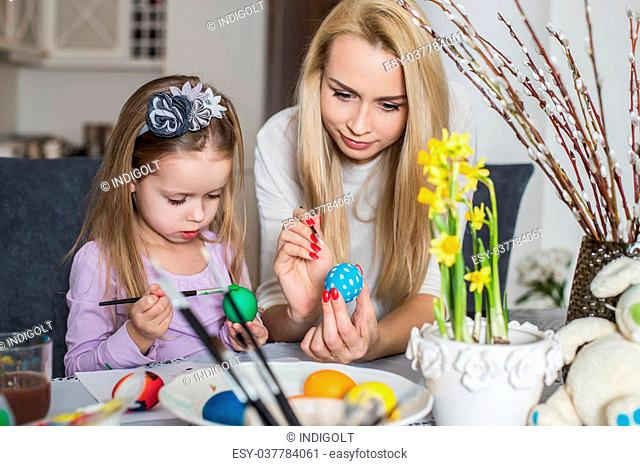 Girl with her mother learning to paint Easter eggs. Cozy home atmosphere. Easter