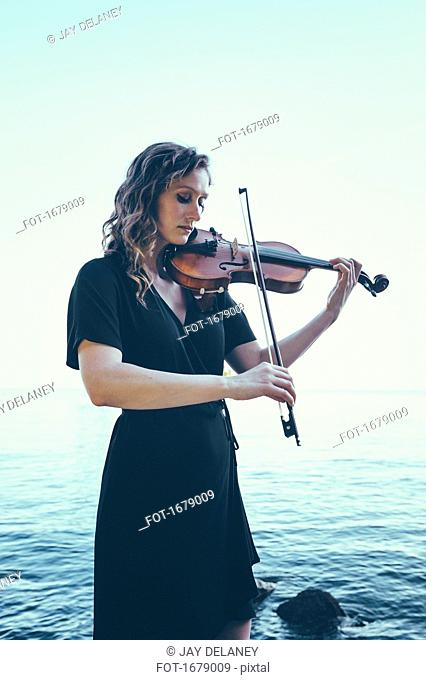 Beautiful young woman playing violin while standing by lake against clear sky