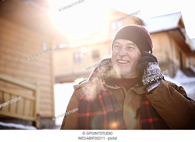 Smiling senior man talking on cell phone in mountain village in winter