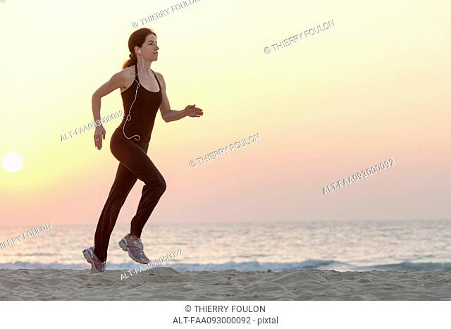 Woman jogging on beach at sunrise with earphones