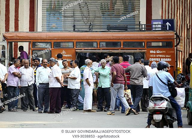 Bangalore, India - October 23, 2016: Large group of people buying hot coffee from a mobile canteen while other stand aside in the Avenue road